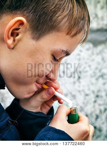 Teenager secretly smokes the Cigarette on the Street closeup