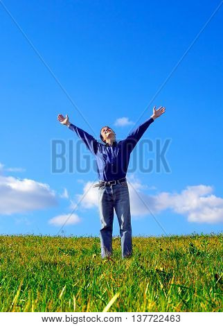 Happy Young Man with Hands Up in the Field