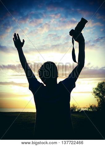 Happy Man Silhouette with Photo Camera on the Sunset Background