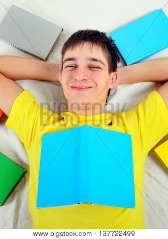 Cheerful Teenager with a Books on the Bed