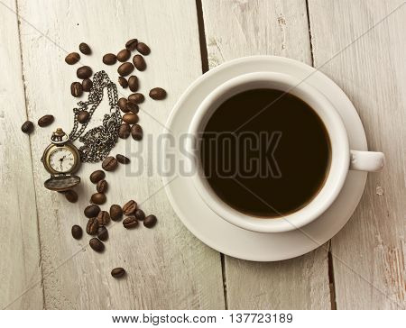 A cup of black coffee with coffee beans and a vintage chain watch shot from above on a wooden board texture slightly toned; coffee time concept