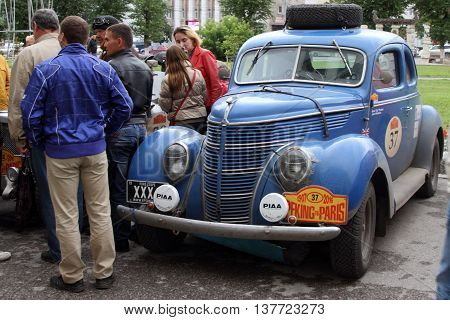 PERM RUSSIA - JUNE 29 2016: Rally of retro-cars Peking-Paris 2016 June 29 2016 in Perm Russia. Residents inspect the cars of all participants.