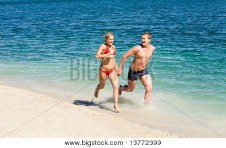 Portrait of woman and man running together along beach