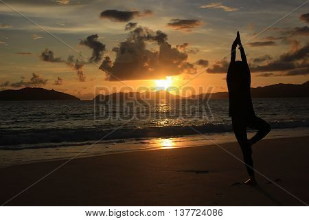 a man is dancing at the evening sunset on the beach