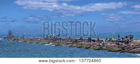 illustrative image of fishermen on a rock jetty in Gulf of Mexico.