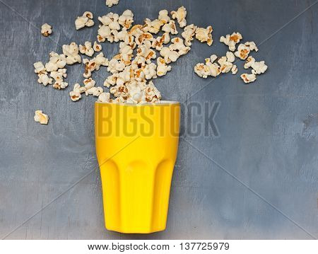 popcorn chaotic jumps from big yellow cup on a blue background
