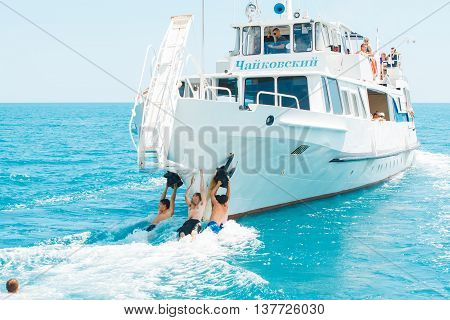 YALTA UKRAINE- JULY 09 2012: Teenagers having fun clinging to a departing pleasure boat July 09 2012 Yalta Ukraine