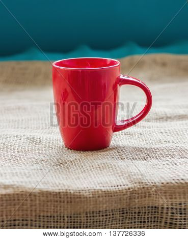 Red Cup On A Table By The Window On Sackcloth Isolated, With A Hot Drink Invigorating