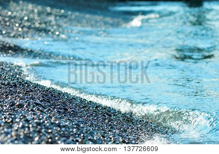 Black sea stones background. Glossy round river rocks and wave surfin.Sea pebbles wave coast.