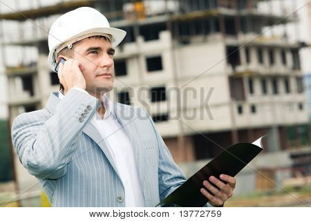 Portrait of worker speaking on the phone at building site
