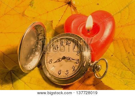 Antique watch with raindrops on the face and red heart-shaped candle against the background of autumn leaves (retro style)
