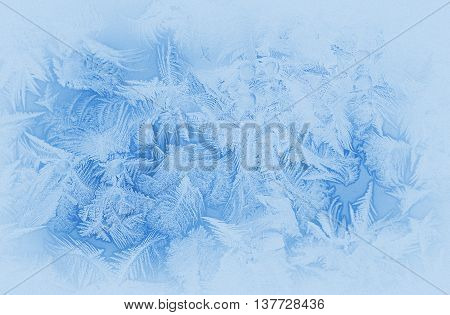 Bright blue frost pattern on a window glass in the winter (as an abstract winter background) retro style