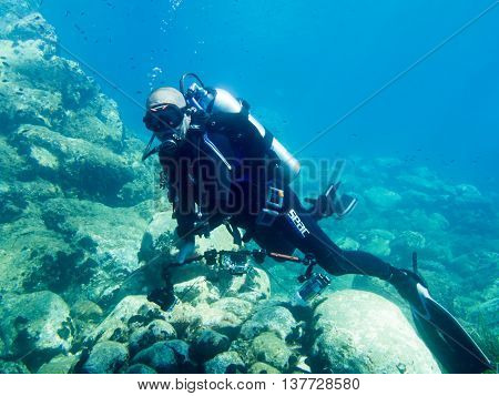 Avlaki Greece - June 15 2016 : A male scuba diver with a camera shows good buoyancy during a dive