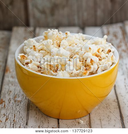 Fresh popcorn in yellow bowl on white wooden table. Selective focus.