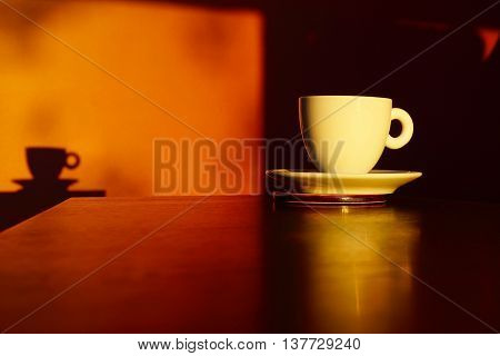 Cup and saucer of coffee with dramatic light and shadow