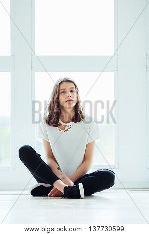 Lost In Thoughts. Young Beautiful Brunette Hipster Woman Sitting On Floor Near Huge Window And Looki