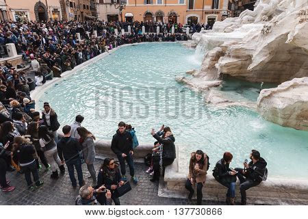 Rome Italy - February 13 2016: Many tourists visiting the Trevi Fountain an iconic symbol of Imperial Rome. It is one of the most popular tourist attractions in Rome