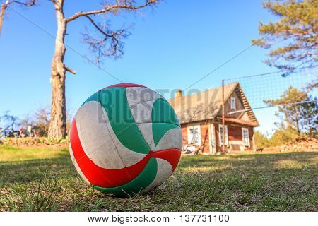 Sport equipment. Volleyball on courtyard of an old wooden house on the grass.