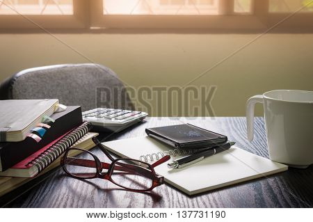 Smartphone put down on table beside notebooks and pen in morning time on work day. Business working at home concept