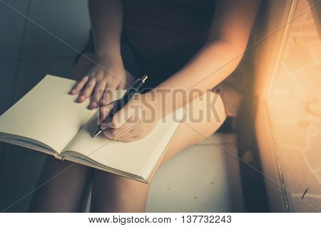 Young woman left hand writing on blank book while sitting beside window in morning time on weekend. Morning lifestyle on weekend concept with vintage filter effect