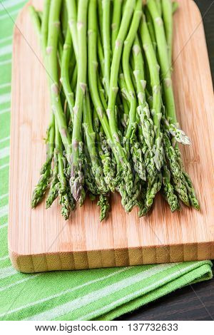 Close up of fresh asparagus on wooden board. Selective focus on tips of asparagus.