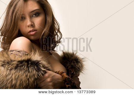 Portrait of temptress wearing fashionable dress and posing before camera during photo shoot