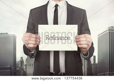 Refinance on paper what businessman is holding on cityscape background