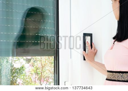 Woman is covering the window by blind