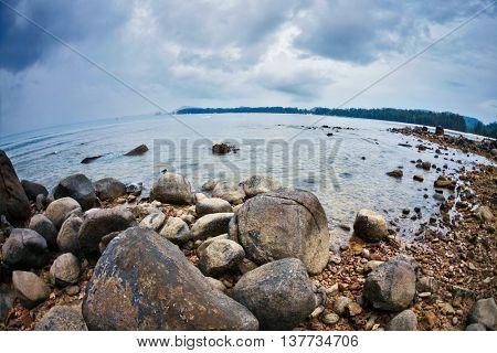 fisheye view on beach and tropical sea under gloomy sky