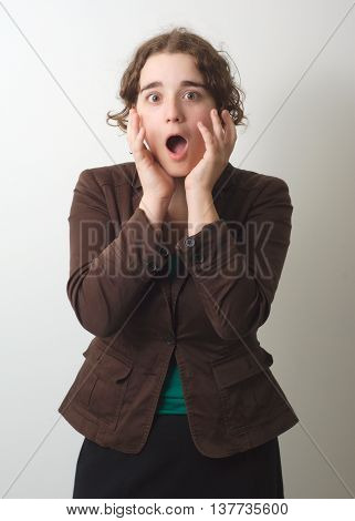 young girl surprised or horrified on gray background