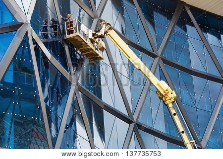 MINSK BELARUS - MAY 03 2016: Renaissance Minsk Hotel - this is the first hotel of the well-known international hotel chain Marriott in Belarus. Woman washes windows of a modern building.