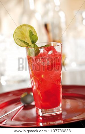 Red mojito prepared with campari orange sugar mint leaves and lemon-lime soda drink.