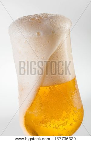 Draft beer overflowing in a tulip glass