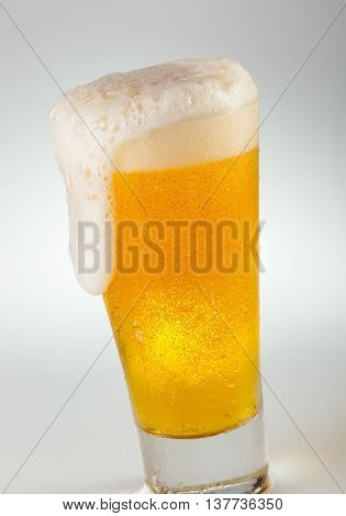 A delicious refreshing glass of foamy draft beer.