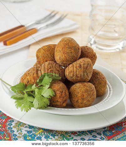 Falafel balls served on a plate at a restaurant.
