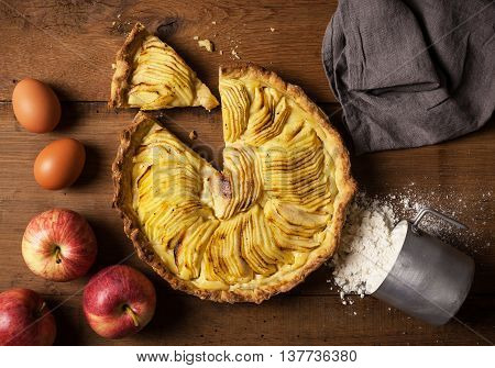 Homemade apple pie on a natural wood table with apples eggs and flour