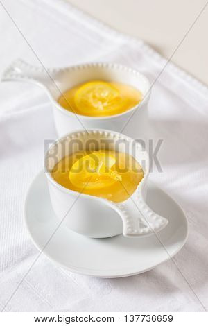 Two bowls of a lemon custard dessert on a white table