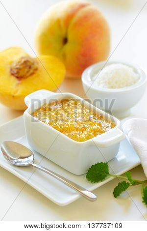 Peach jam with coconut and fresh peaches on a table.