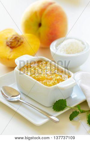 Peach jam with coconut and fresh peaches on a table.