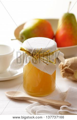 A jar of homemade pear jam and ripe pears on a breakfast table.