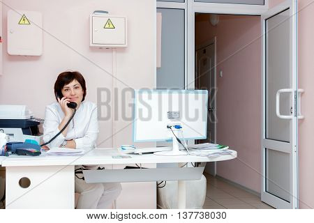 Yekaterinburg Russia - May 25.2016 Female doctor talking on the phone in the reception room of clinic