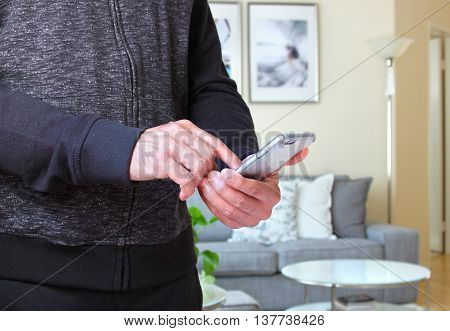 Male using smarphone with background of the room interiors
