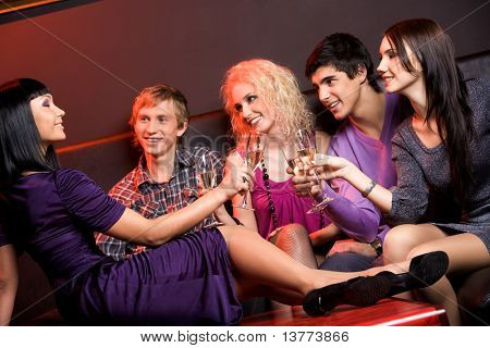 Group of friends looking at gorgeous girl sitting on table with flute full of champagne
