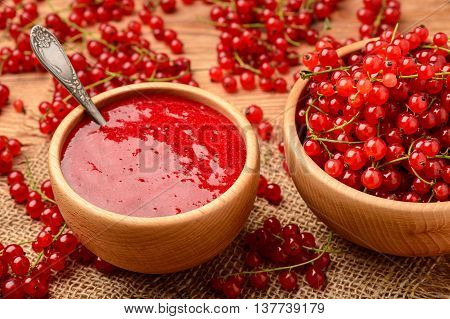 Red currants jam in wooden bowl. Selective focus.