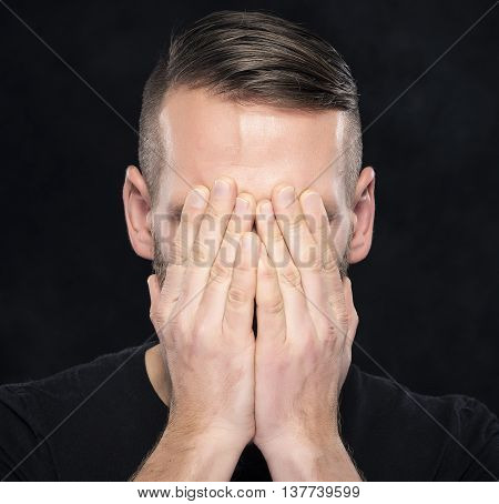 Man covers face with hands on dark background.