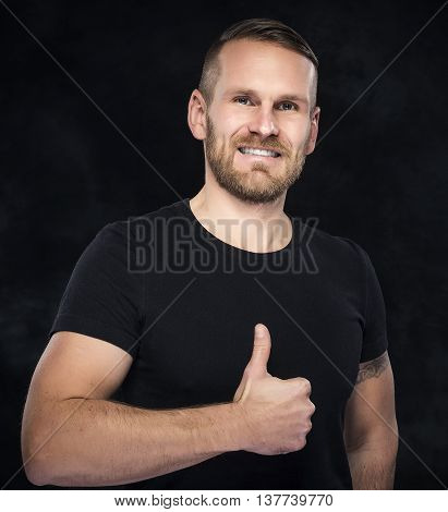Mascular man showing thumb-up over dark background.