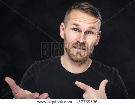 Young man in a misunderstanding on dark background.
