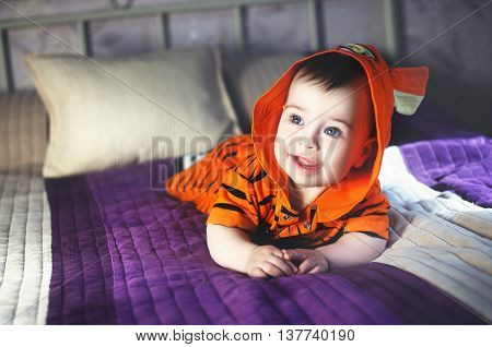 Little cute child in tiger pijama smiling on the bed