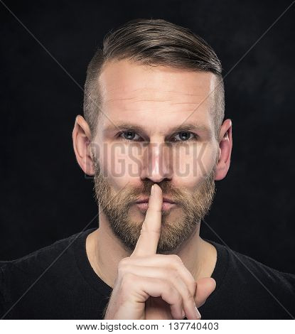 Man gesturing silence, quiet, on dark background.