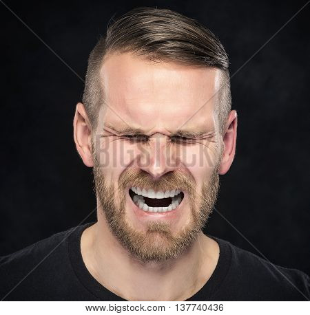 Young man screaming on a dark background.